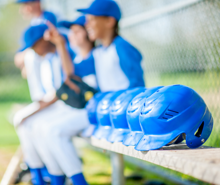 Little League Sponsorship Article - Row of blue baseball helmets on bench next to young baseball players